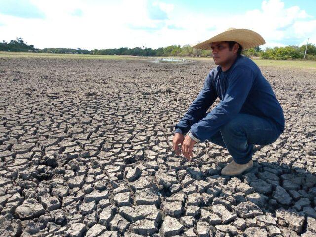 Homem agachado sobre terra seca