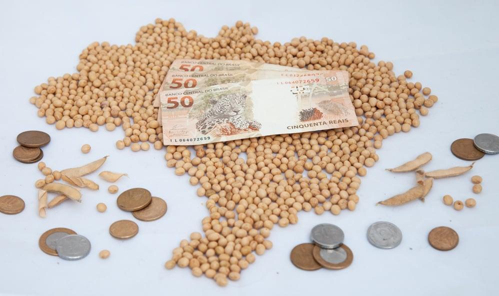 Monte de soja em grão formando mapa do Brasil. Sobre ele, três notas de 50 reais. Ao redor, moedas de diversos valores