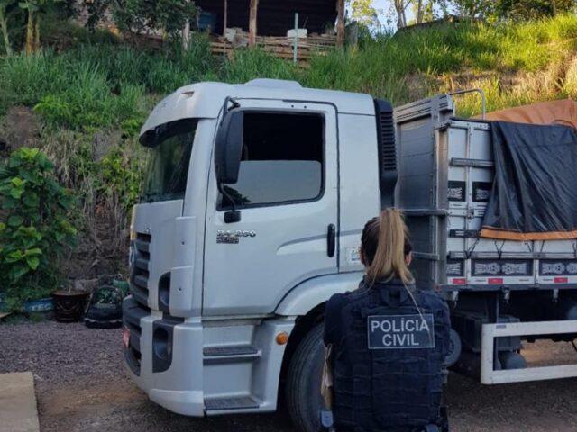 Policial civil na frente de caminhão usado para transportar cargas de grãos furtadas